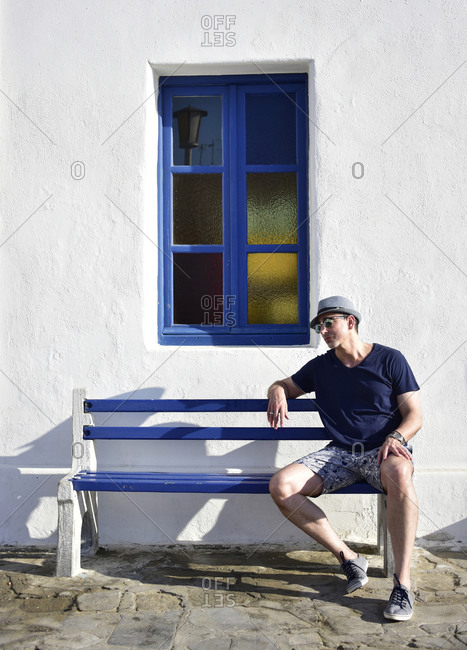 Tourist in Mykonos on Bench with Window