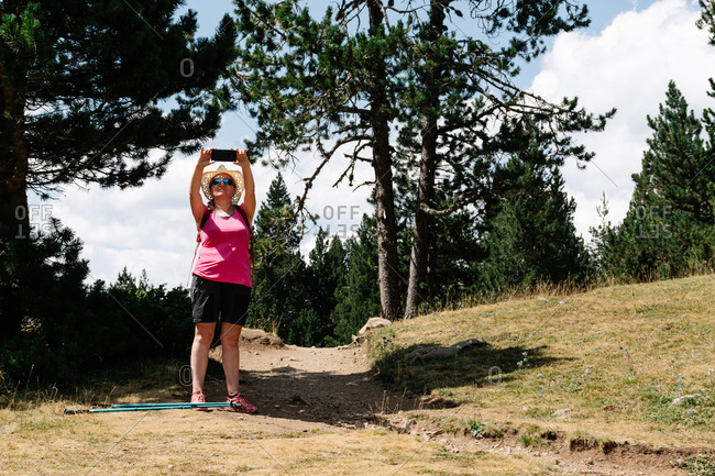 Hiker woman wearing straw hat, shorts and backpack on the path in a forest of pine trees takes a photo