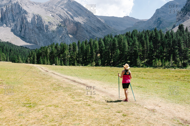 Back view of hiker woman wearing straw hat, shorts and backpack on the path across a plain with mountains in the background