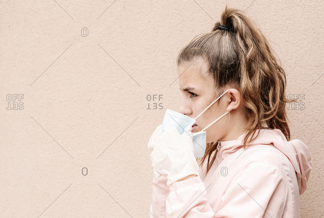 Young blonde girl wearing latex gloves putting on her face mask to protect herself from the coronavirus