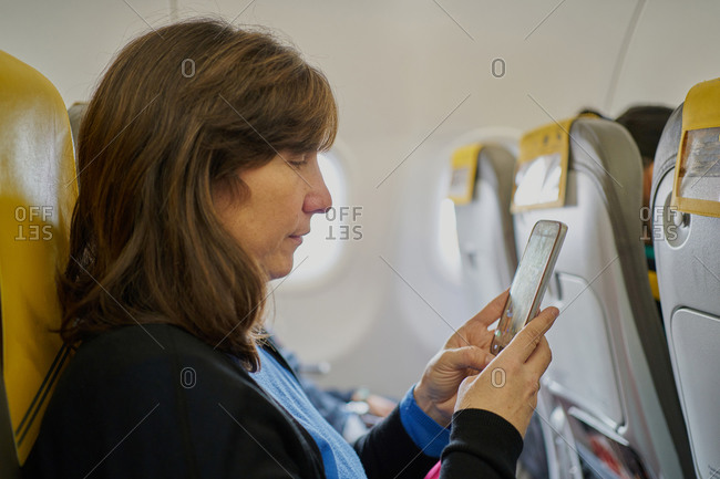 caucasian female passenger looking at her cell phone on a commercial flight