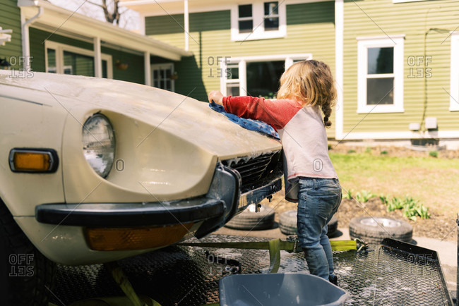 Toddler girl washing a classic car.