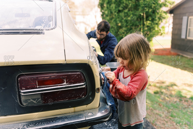 A father and his toddler daughter washing a classic car together.