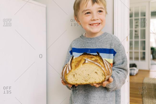 Cute little preschooler holding a homemade loaf of sourdough bread.