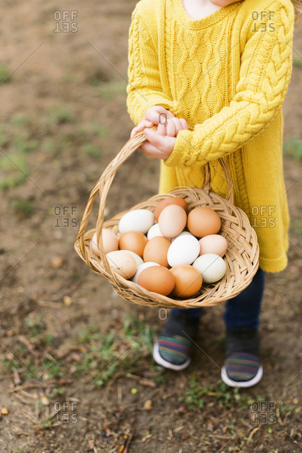 Little toddler girl holding a basket of farm fresh eggs.