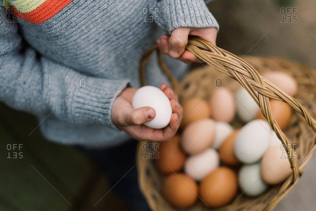 Little boy holding a basket of farm fresh eggs.