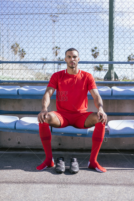 Portrait of African American male soccer player sitting on bench
