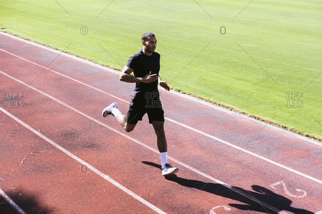 Pulled back view of African American athlete running on track