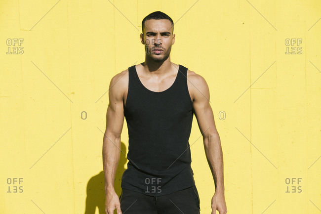 Portrait of African American athlete against bright yellow wall