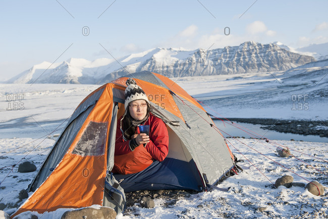 Woman drinking hot beverage at winter camp in Iceland
