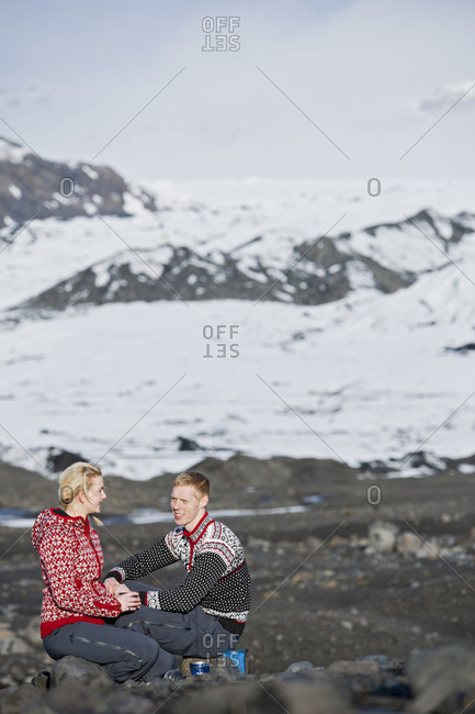 Young couple having a picnic in barren landscape in Iceland