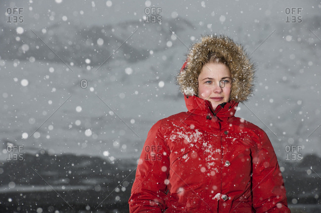 Young woman walking through snowstorm in Iceland
