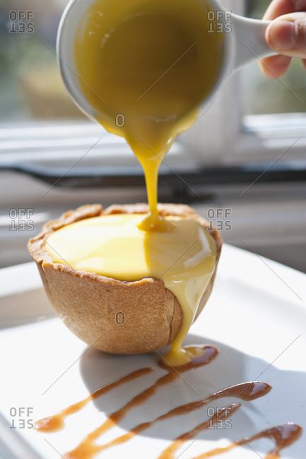 Custard poured over apple tart at British pub