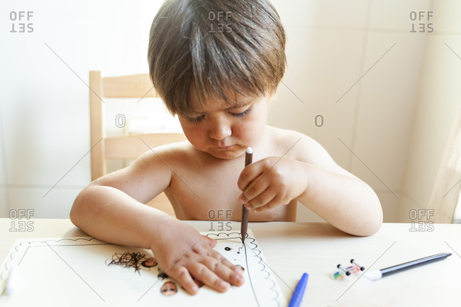 Shirtless little boy sitting on table drawing at home