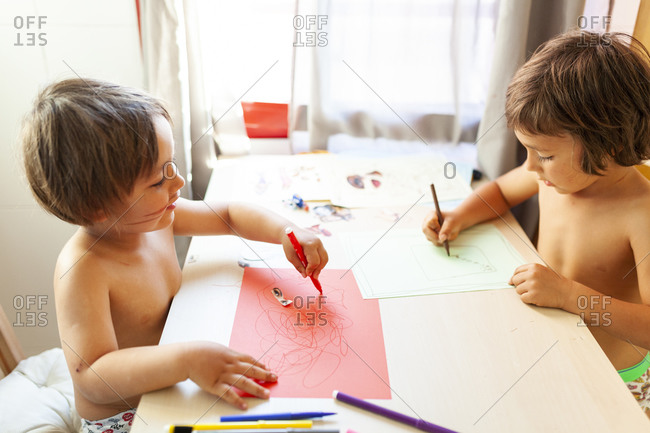 Two little boys making art work at home during summertime