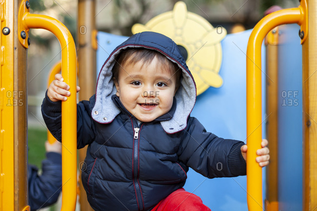 Happy  little kid  plays on colorful playground equipment