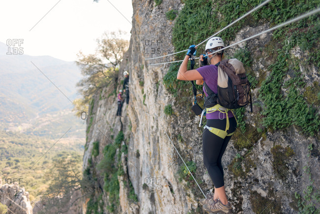 Woman with helmet, harness and backpack. Walking on a Tibetan bridge.