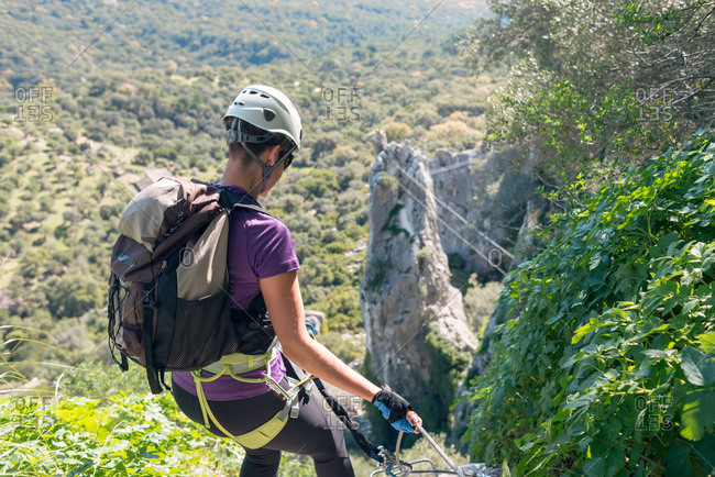 Woman with helmet, harness and backpack. Descending in the mountains via ferrata.