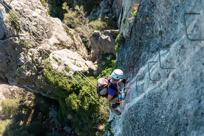 Woman with helmet, harness and backpack walking down via ferrata in the mountains.
