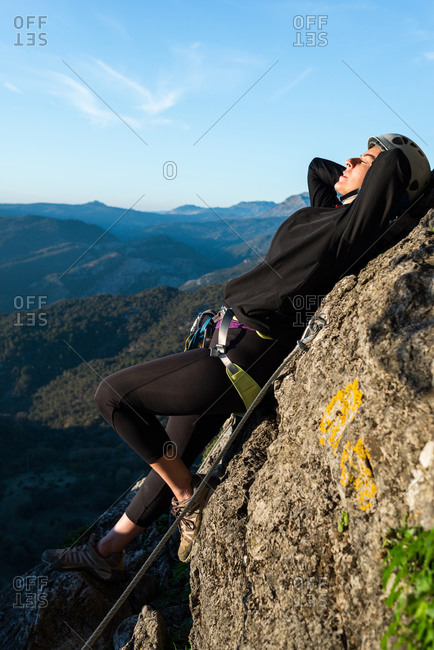Climber woman with helmet and harness. Lying on a rock taking a sunbath. Via ferrata in the mountains.