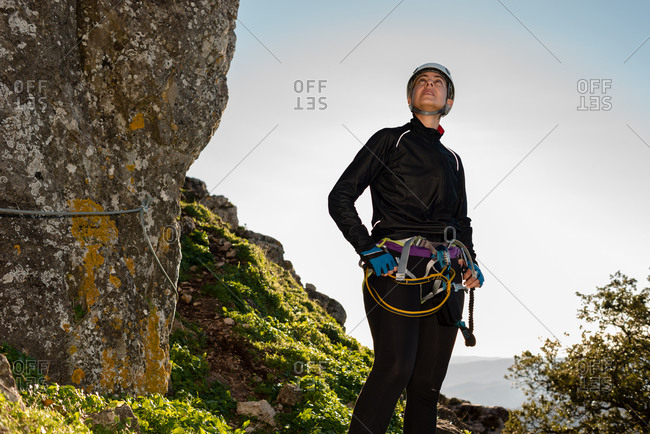 Climber woman with helmet and harness. Pensive standing on a rock. Looking at the top of the mountain.