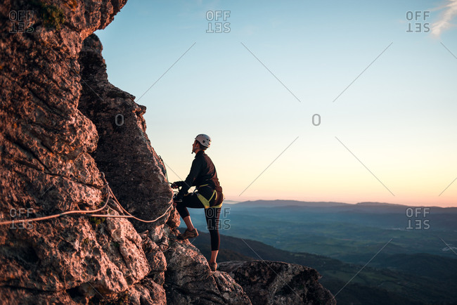 Climber woman with helmet and harness examining path