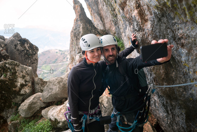 Pair of climbers with helmet and harness taking a selfie with smartphone.