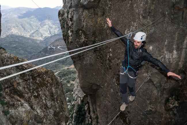 Climber balancing on a Tibetan cable bridge