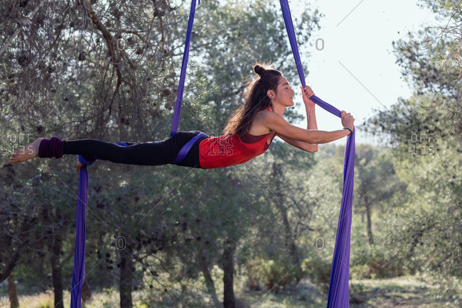 Young girl acrobat. Practicing aerial silks. Woman doing stunts with clothes in the forest. Horizontal position.