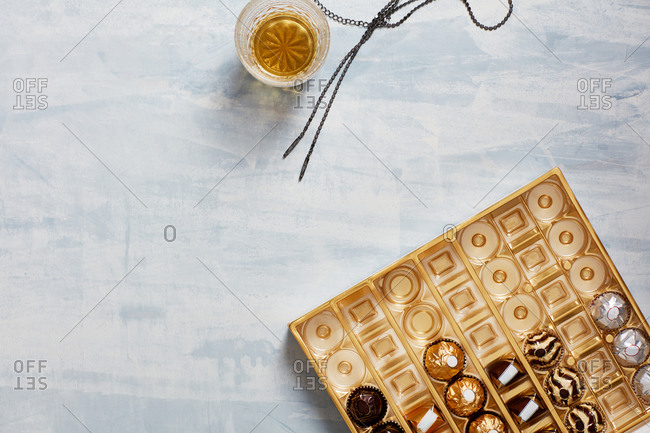 Still life of box of opened chocolates, whisky glass, necklace