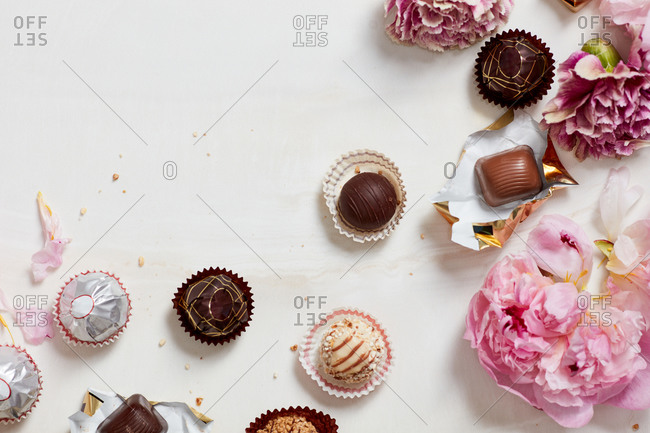 Still life of open chocolates and wrappers with flowers