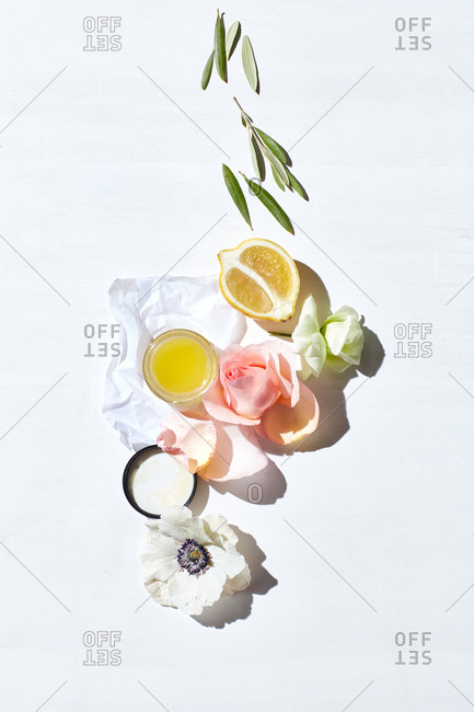 Still life of skin care products, fresh lemon, flower pedals