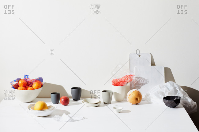 Still life with fruits, pottery cups and surfaces
