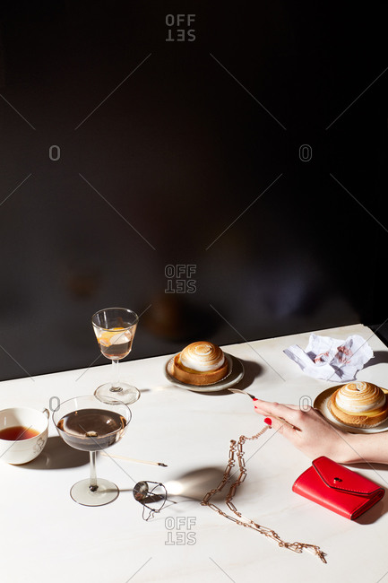 Still life of clutch purse, woman's hand and after dinner deserts