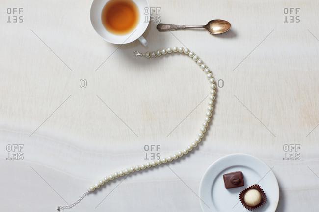 Still life of necklace, tea cup, chocolates
