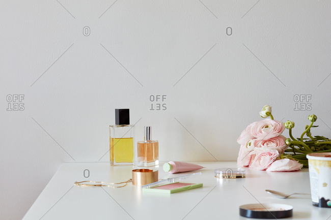 Still life with perfume bottles, beauty products, ice cream, roses