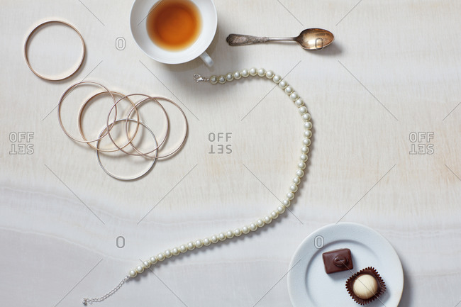 Still life with tea cup, jewelry, necklace, chocolates
