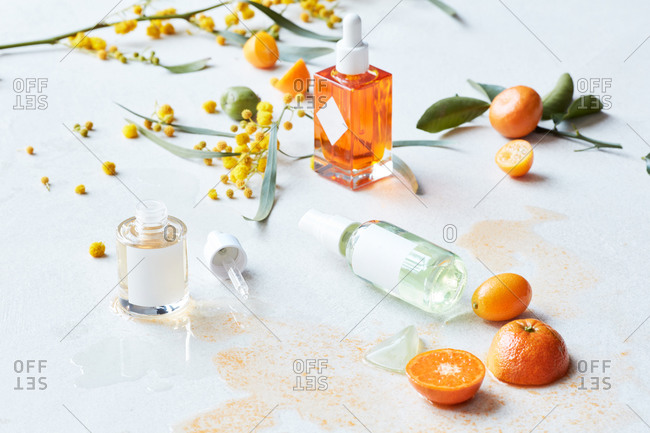 Still life display of skin care products with fruits and branches