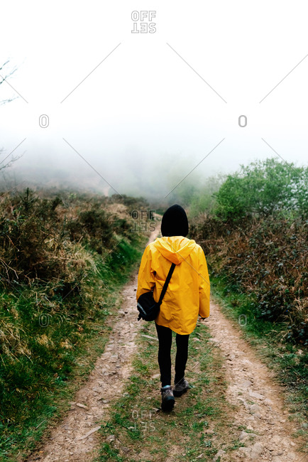 Full length back view of anonymous tourist in bright yellow raincoat and black hood with handbag walking alone along dirt road among green and dry brown bushes in misty countryside