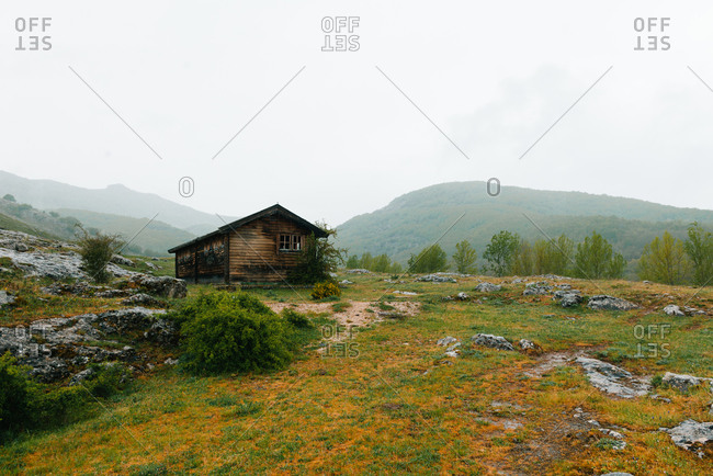 Lonely house in mountainous valley in overcast day