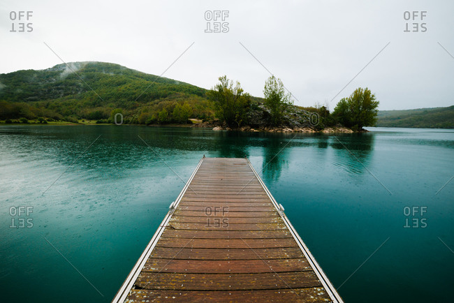 Landscape with wooden planked footway in calm lake water against forest