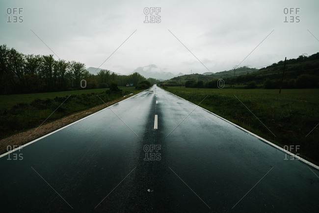 Countryside road among mountainous terrain with green forest
