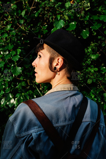 Back view of young stylish lady with stylish black hat standing near blooming bushes and looking away