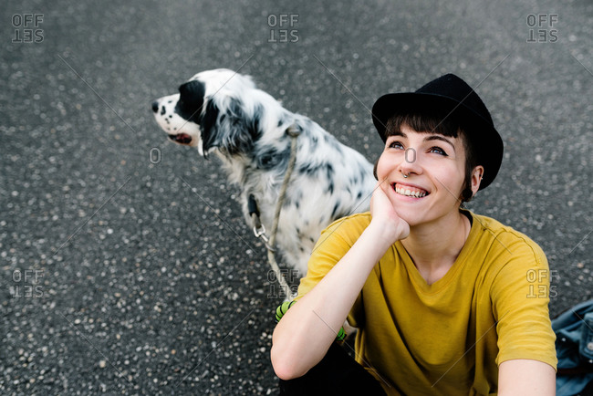 From above positive young lady in casual clothes and black hat resting on ground with dog during walk in park
