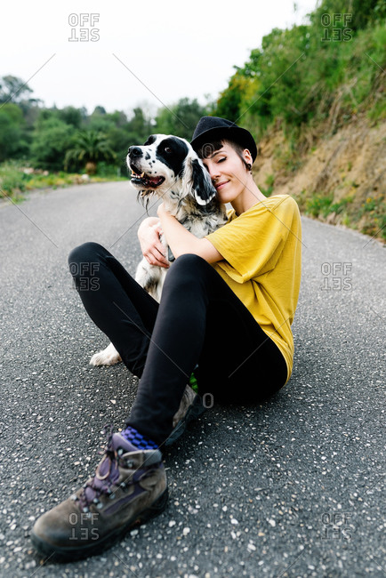 Cheerful young lady in casual clothes and hat sitting on ground with her dog during walk on street