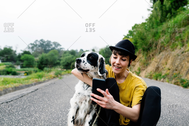 Cheerful young lady in casual clothes and hat sitting on ground with mobile phone and taking selfie with dog during walk on street