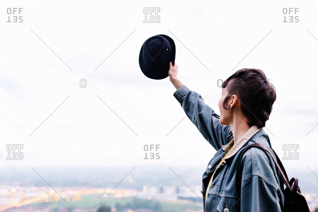 Side view of unrecognizable young lady in casual clothes with backpack and hat standing on hill with raised hand and admiring cityscape while spending time in evening