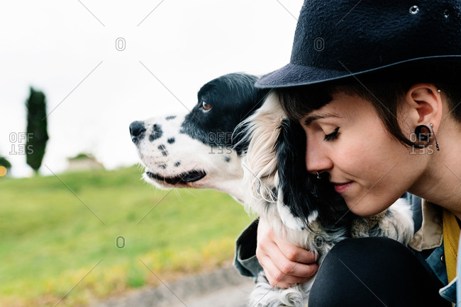 Cheerful young lady in casual clothes and hat sitting on ground hugging her dog during walk on street