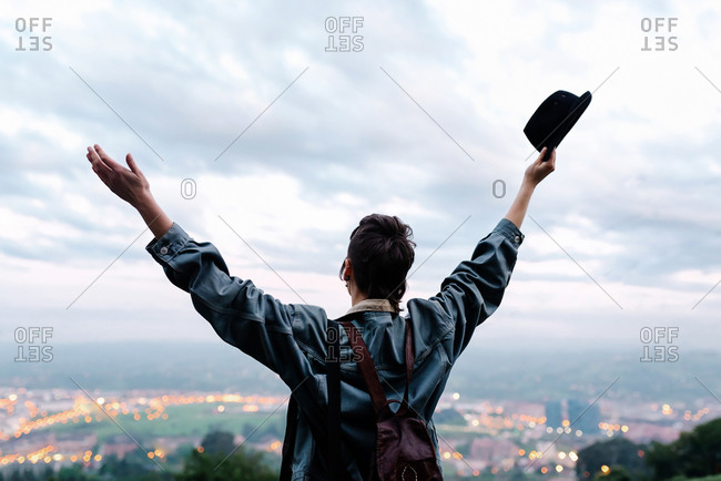 Back view of unrecognizable young lady in casual clothes with backpack and hat standing on hill with raised hands and admiring cityscape while spending time in evening