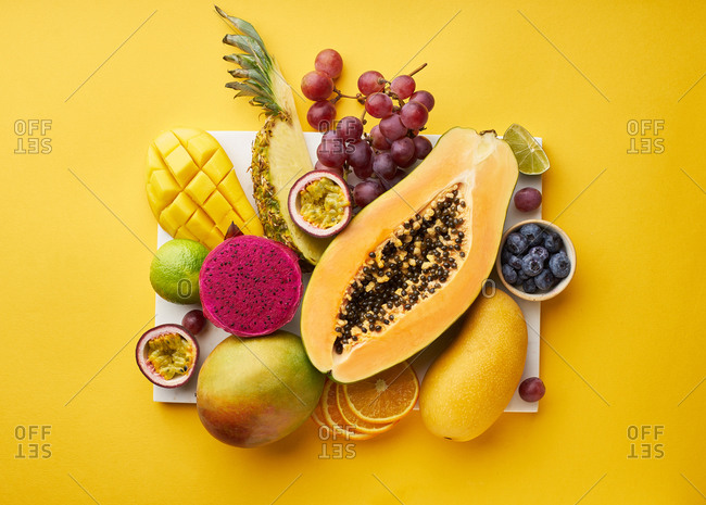 Top view of flat lay with tropical fruits on a tray: papaya, mango, dragon fruit and pineapple on yellow background. Summer treat